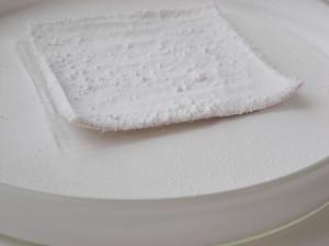 Prøve af moderne uldstof imprægneret med cyclododecan. Hjørnerne på stoffet trækkes op og viser at stoffet vil have skadelig virkning, hvis det blev brug til at stabilisere kjolen under vending.